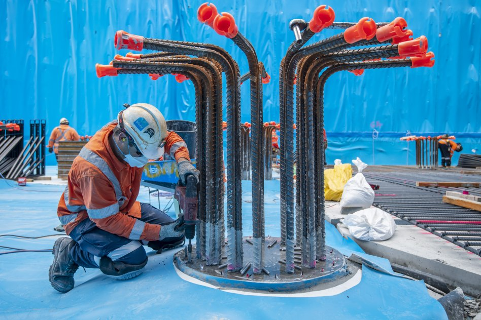 A worker drills bolts to secure the waterproofing to the top of one of the 99 piles installed in three rows down the entire 200-metre long station floor.